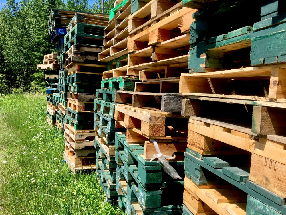 Block pallets vs. stringer pallets: piles of different kinds of wood pallets stacked side by side.