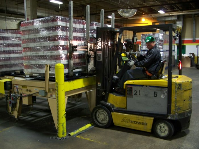 A forklift picks up a 4-way pallet.