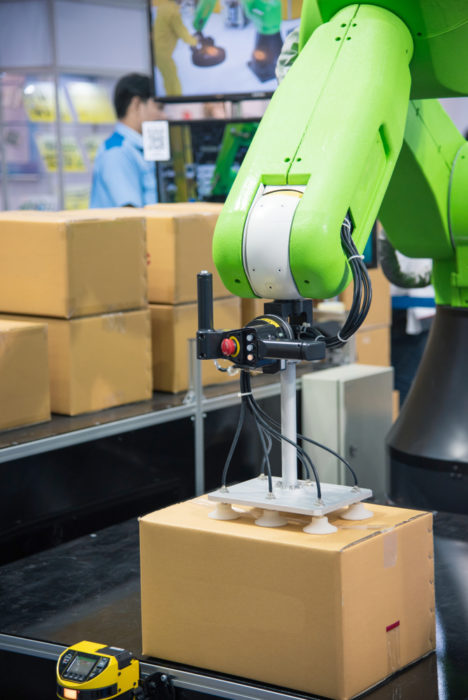 A robotic arm lifts packages onto pallets