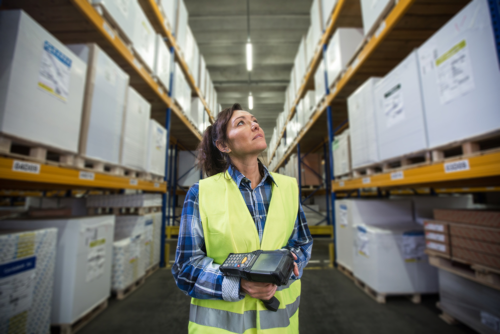 Woman in supply chain warehouse with scanner for tracking